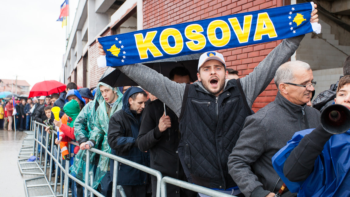 A fan cheering for Kosovo while waiting to enter the stadium
